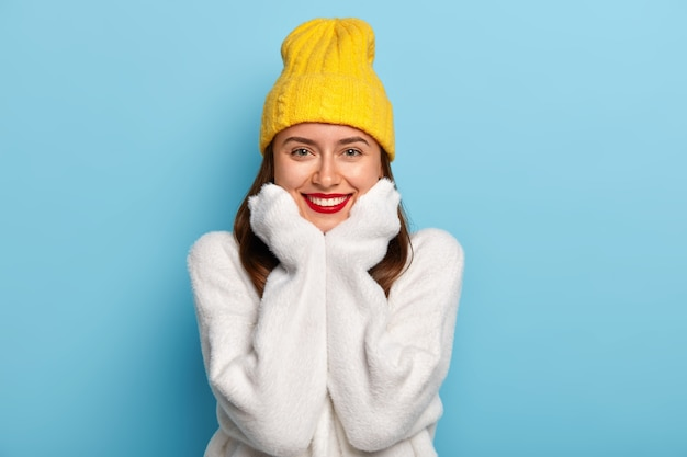 Portrait of happy female with red lips, white perfect teeth, beaming smile, wears comfortable long sleeved sweater