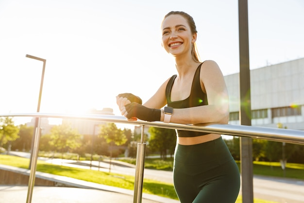 Portrait of happy fitness woman wearing tracksuit smiling and leaning on railing while walking through green park during workout