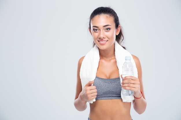 Portrait of a happy fitness woman with towel holding bottle with water isolated on a white wall