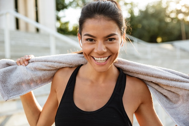 Portrait of a happy fitness woman with towel resting
