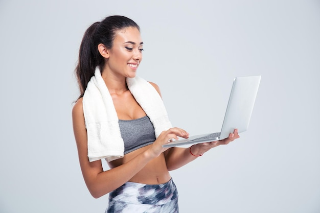 Portrait of a happy fitness woman with towel using laptop computer isolated on a white wall