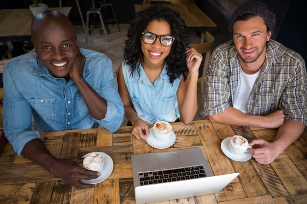 Portrait of happy friends having coffee with laptop on table in cafe