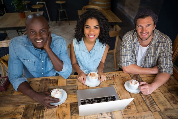 Portrait of happy friends having coffee with laptop on wooden table in cafe