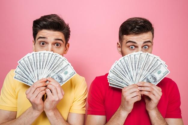 Portrait of a happy friends holding money