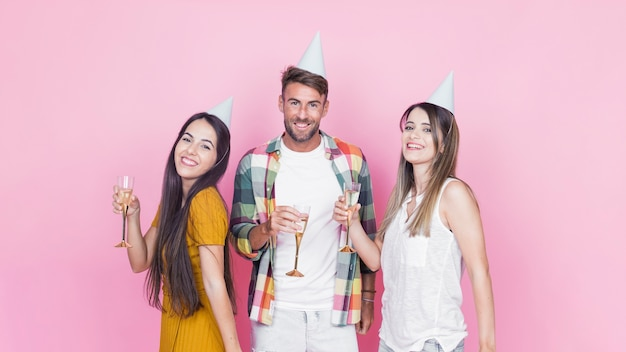 Portrait of happy friends holding wineglasses on pink background
