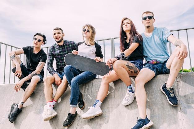 Portrait of happy friends sitting on ramp