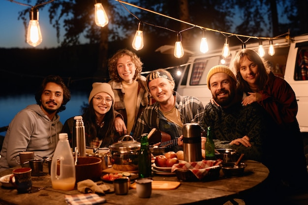 Portrait of happy friends smiling at camera while sitting at dinner table during camping in the forest