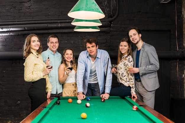 Portrait of happy friends standing behind snooker table enjoying in club