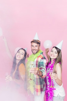 Portrait of happy friends with wineglass dancing on pink background