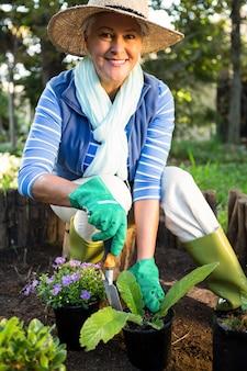 Portrait of happy gardener planting at garden
