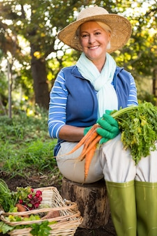 Portrait of happy gardener with carrots sitting at garden