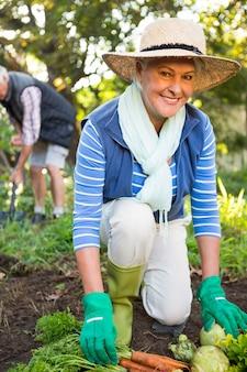 Portrait of happy gardener with colleague working at garden