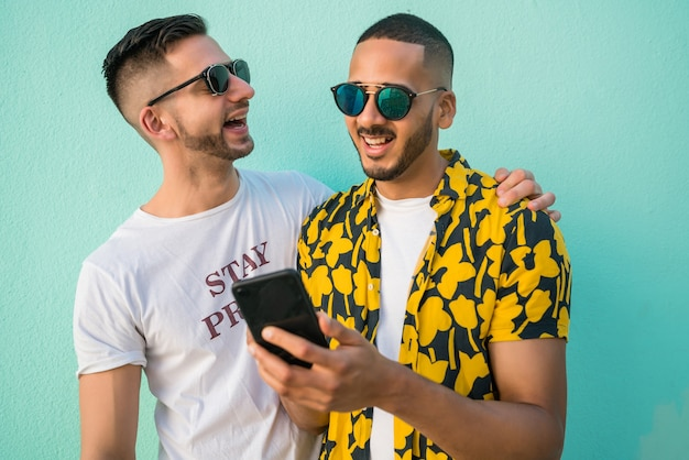 Portrait of happy gay couple spending time together while using mobile phone. lgbt and love concept.