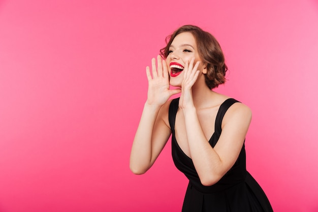 Portrait of a happy girl dressed in black dress shouting