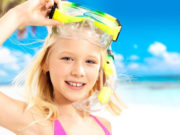 Ritratto della ragazza felice che gode alla spiaggia. ragazza di scolaro con maschera da nuoto sulla testa.