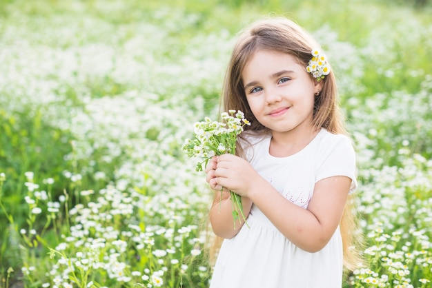 Portrait of happy girl holding white flowers in her hand