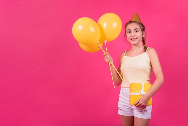 Portrait of a happy girl holding yellow gift box and balloons in her hand over pink background