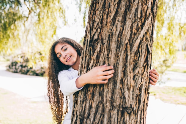 Portrait of a happy girl hugging large trunk in the garden
