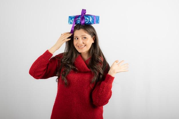 Ritratto di una ragazza felice che mette una confezione regalo sulla sua testa.