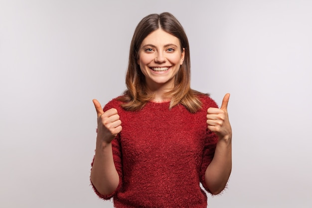 Portrait of happy girl in shaggy sweater looking at camera with toothy smile and showing thumbs up