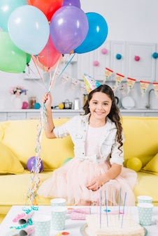Portrait of happy girl sitting on sofa holding colorful balloons