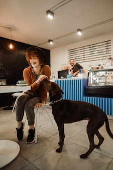 Portrait of happy girl sitting at table in cozy cafe with cup of coffee and playing with dog