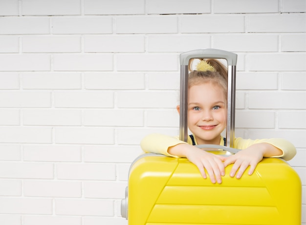Portrait of a happy girl tourist with a yellow suitcase for traveling on a white bricks background