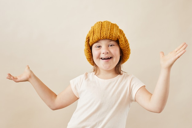 Portrait of happy girl with down syndrome wearing warm hat smiling at camera against the white background