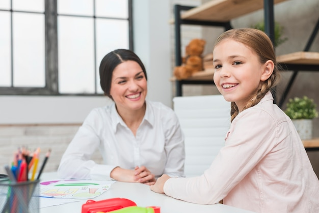 Portrait of a happy girl with her young female psychologist in office