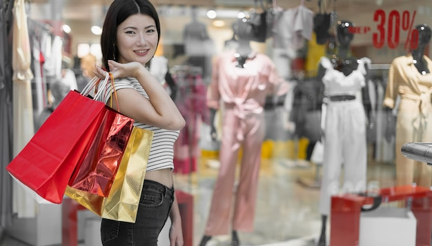Portrait of happy girl with paper bags looking at camera in shopping mall. shop window of women's clothing
