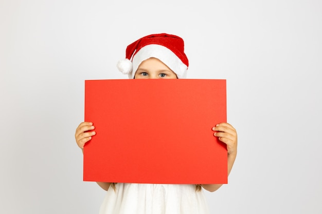 Portrait of happy girl with santa claus hat hiding behind red empty poster in hands isolated on whit...