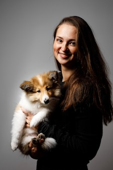 Portrait of happy girl with sheltie puppy.