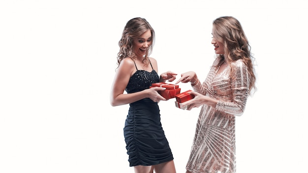 Portrait of happy girls friends exchanging presents isolated on white