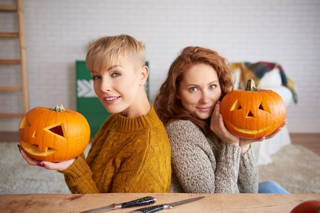 Portrait of happy girls holding pumpkins