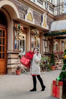 肖像画幸せな格好良い女性は、彼女の手にギフトボックスを持って、屋外に立っている間笑顔です。クリスマスプレゼントでポーズをとって美しい幸せな女の子。新年の準備。