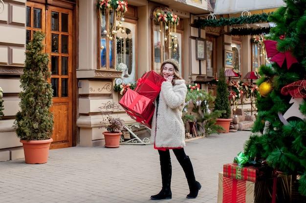 세로 행복 잘 생긴 여자는 그녀의 손에 선물 상자를 잡고 야외에 서 있는 동안 웃 고. 크리스마스 선물과 함께 포즈를 취하는 아름 다운 행복 한 소녀. 새해 준비.