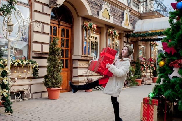 세로 행복 잘 생긴 여자는 그녀의 손에 선물 상자를 들고 서있는 동안 웃고있다
