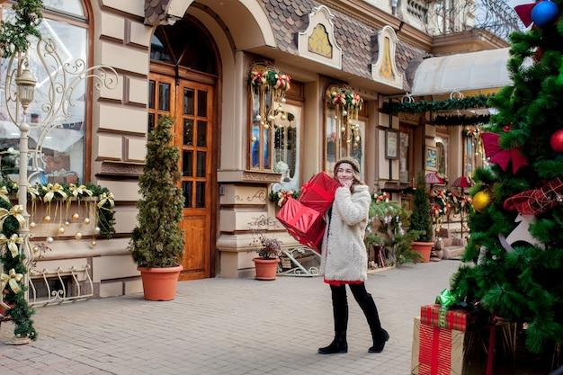 초상화 행복 잘 생긴 여자는 그녀의 손에 선물 상자를 들고 서있는 동안 웃고