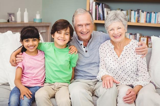 Portrait of happy grandchildren with grandparents at home