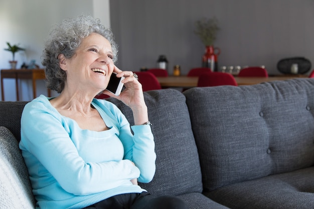 Portrait of happy grandma sitting on sofa and talking on phone