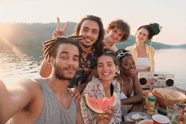 Portrait of happy group of friends smiling and posing at camera they making selfie portrait during picnic outdoors
