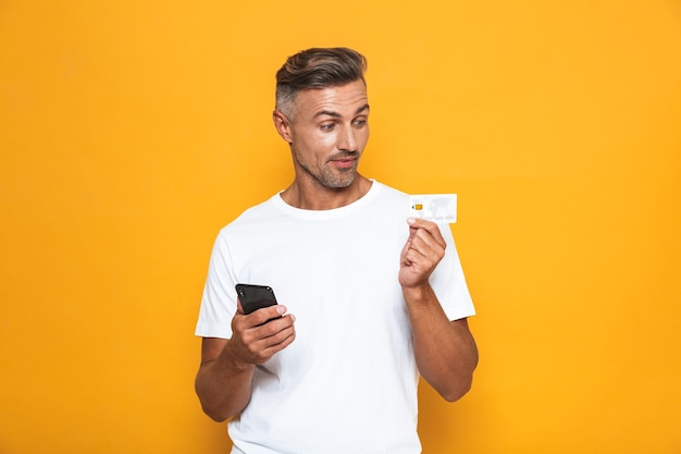 Portrait of happy guy 30s in white t-shirt holding mobile phone and credit card isolated on yellow