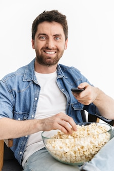 Portrait of a happy handsome bearded man wearing casual clothes sitting in chair isolated, watching a movie, eating popcorn