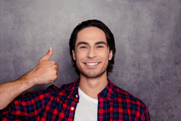 Portrait of happy handsome man showing thumb up