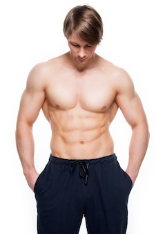 Portrait of a happy handsome man with muscular torso - isolated on white wall.