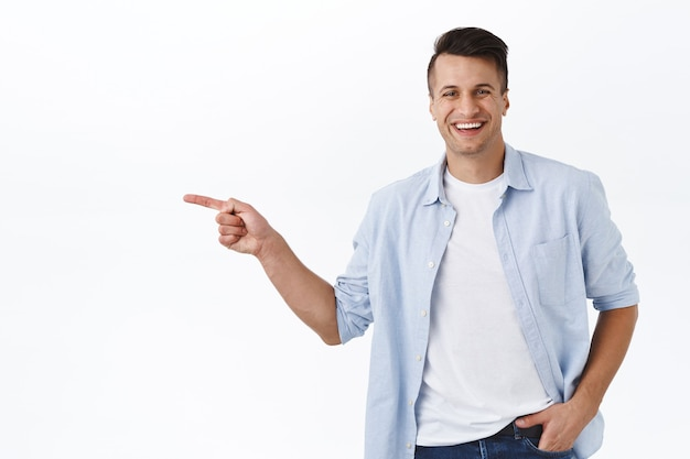 Portrait of happy, handsome masculine adult man pointing finger left and smiling, recommend service or product