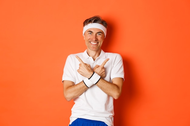 Portrait of happy, handsome middle aged guy in workout clothes, pointing fingers sideways, showing left and right promo banners, orange background.
