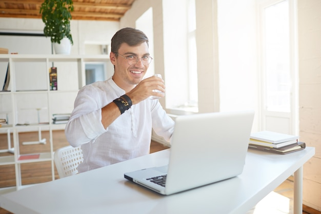 Portrait of happy handsome young businessman wears white shirt at the office
