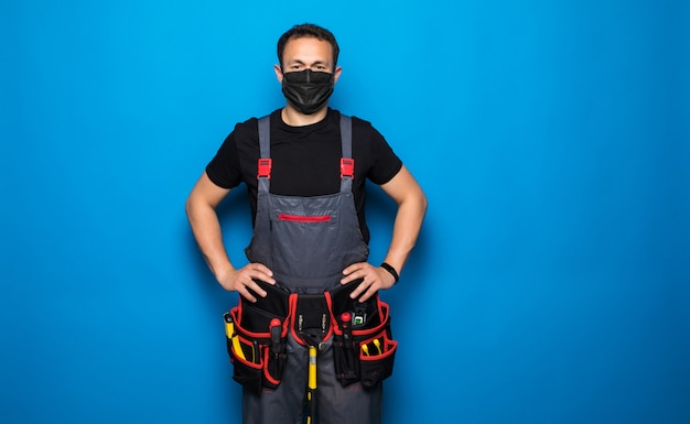 Portrait of happy handyman with medical mask with tools belt