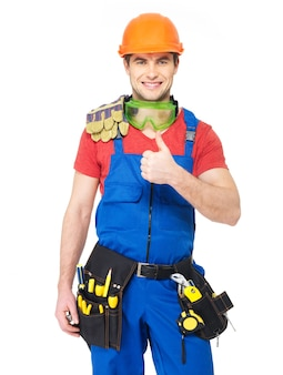 Portrait of happy handyman with tools showing thumbs up sign isolated on white
